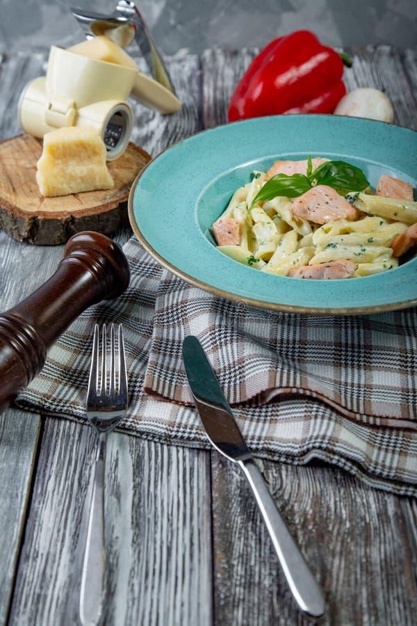 Włoski makaron z smażącymi łososiów polędwicowymi lampasami i łososiowym kremowym kumberlandem składu jedzenia zieleni słoju olej obrazy stock
