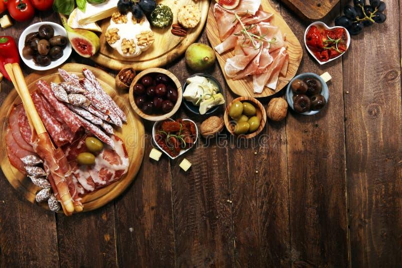 Włoskie antipasti wina przekąski ustawiać Serowa rozmaitość, Śródziemnomorskie oliwki, crudo, Prosciutto di Parma, salami i wino  zdjęcia royalty free
