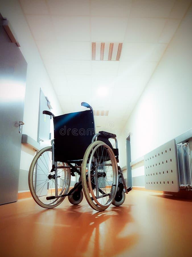 Wózek inwalidzki po środku długiego, pustego szpitalnego korytarza, fotografia stock
