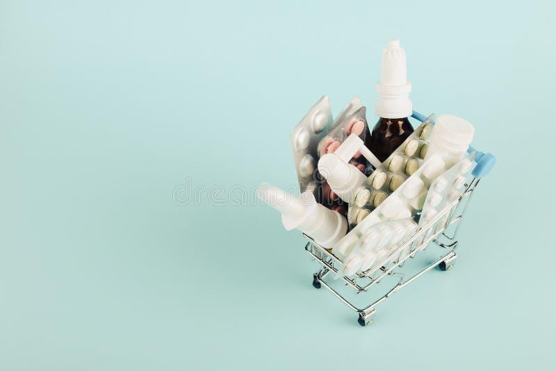 Wózek na zakupy ładował z pigułkami na błękitnym tle Pojęcie medycyna i sprzedaż leki kosmos kopii zdjęcie stock