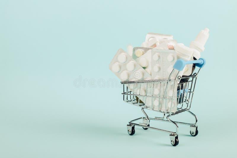 Wózek na zakupy ładował z pigułkami na błękitnym tle Pojęcie medycyna i sprzedaż leki kosmos kopii zdjęcia stock