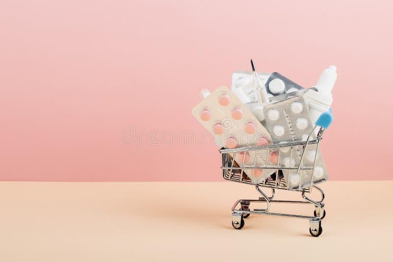 Wózek na zakupy ładował z pigułkami na różowym żółtym tle Pojęcie medycyna i sprzedaż leki kosmos kopii obraz royalty free