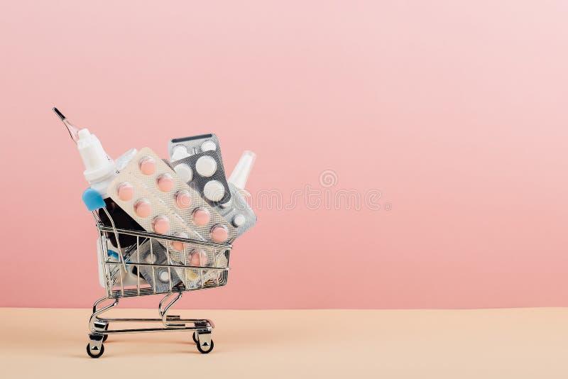 Wózek na zakupy ładował z pigułkami na różowym żółtym tle Pojęcie medycyna i sprzedaż leki kosmos kopii fotografia royalty free