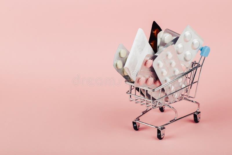 Wózek na zakupy ładował z pigułkami na różowym tle Pojęcie medycyna i sprzedaż leki kosmos kopii obrazy stock