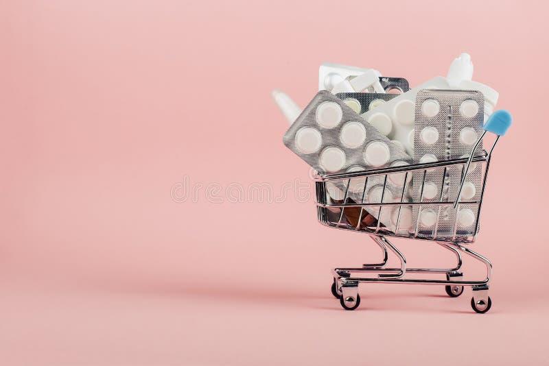 Wózek na zakupy ładował z pigułkami na różowym tle Pojęcie medycyna i sprzedaż leki kosmos kopii obraz stock