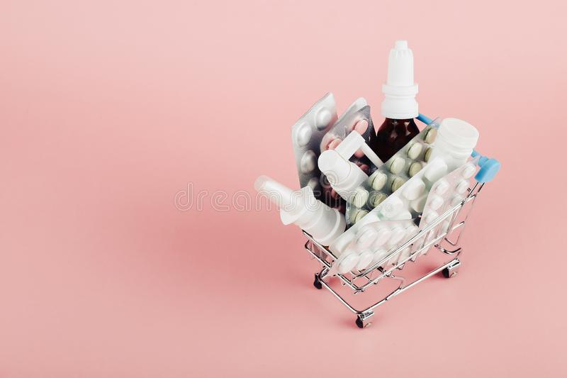 Wózek na zakupy ładował z pigułkami na różowym tle Pojęcie medycyna i sprzedaż leki kosmos kopii zdjęcie stock
