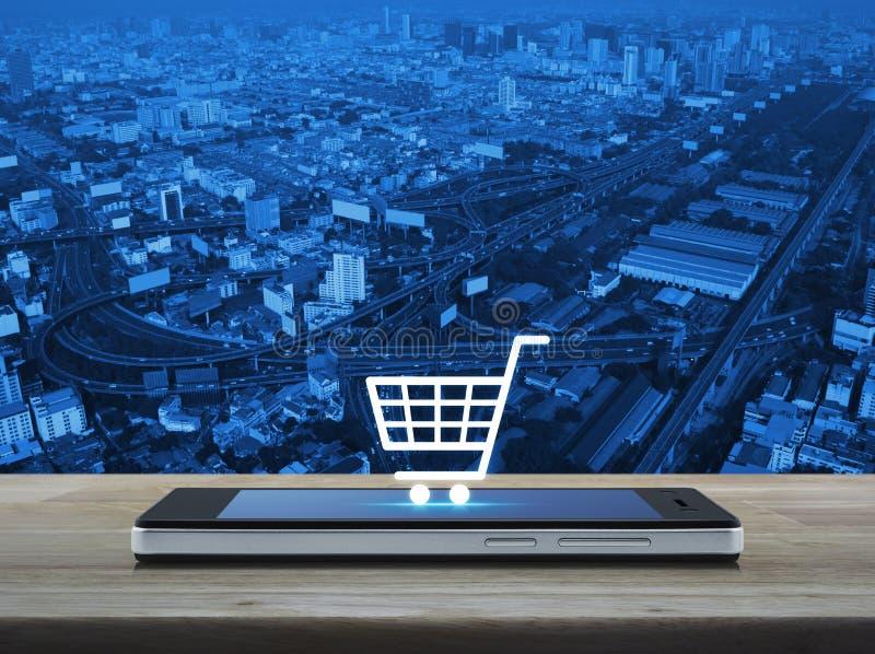 Wózek na zakupy ikona na nowożytnym mądrze telefonu ekranie na drewnianym stole fotografia stock