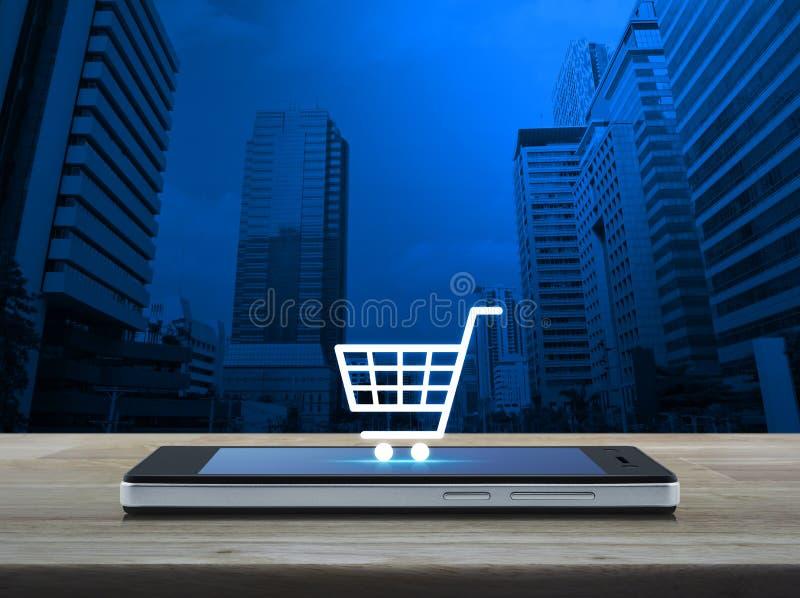 Wózek na zakupy ikona na nowożytnym mądrze telefonu ekranie na drewnianym stole zdjęcie stock