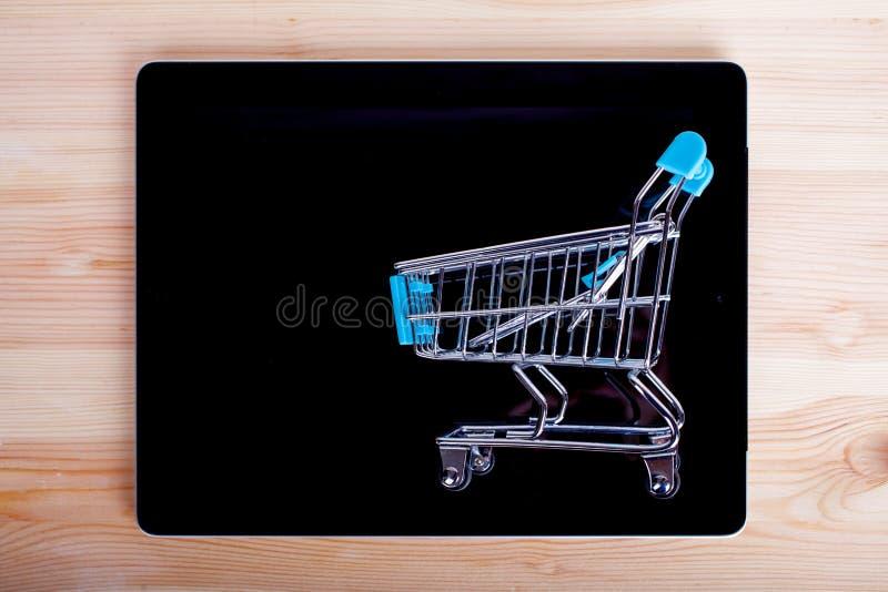 Wózek Na Zakupy nad pastylka pecetem na drewnianym stole, odgórny widok fotografia stock