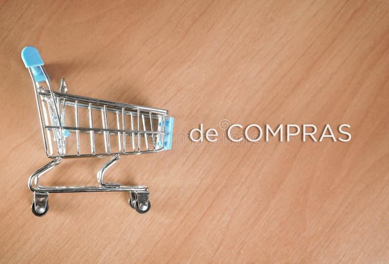 Wózek na zakupy obok go i słowo pisać w hiszpańszczyznach fotografia stock