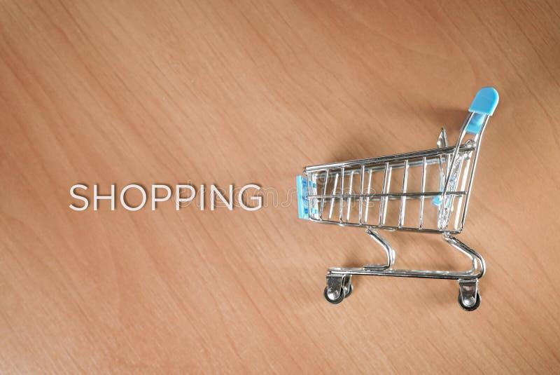 Wózek na zakupy obok go i słowo zakupy zdjęcia stock