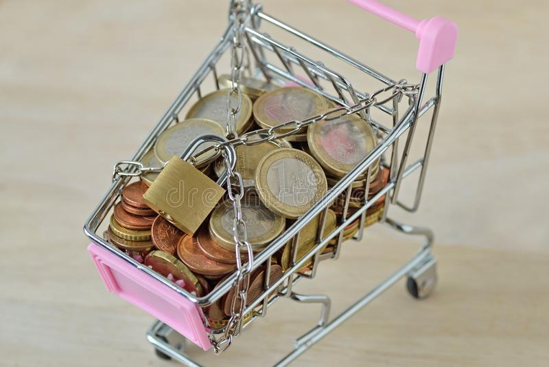 Wózek na zakupy pełno pieniądze z łańcuchem i kłódka - pojęcie oszczędzanie i ochrona, nabywa kryzys obrazy royalty free