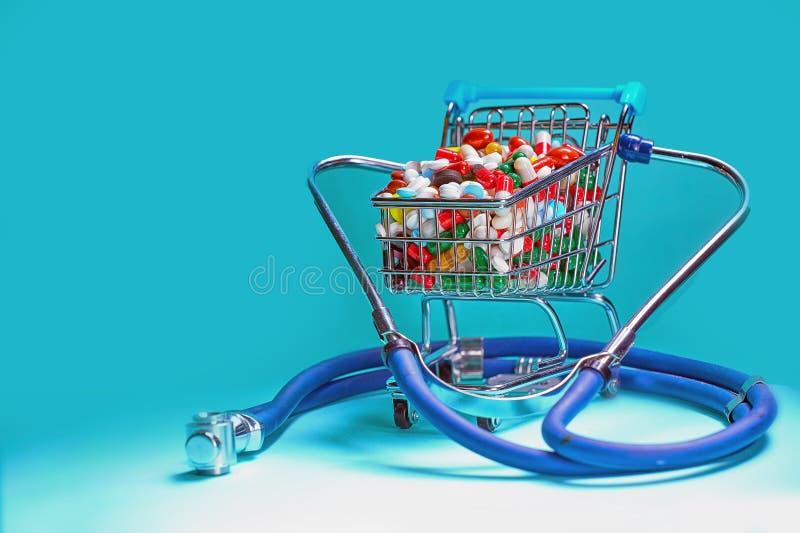 Wózek na zakupy wypełniający z pigułkami z stetoskopem niebieska tła obraz stock