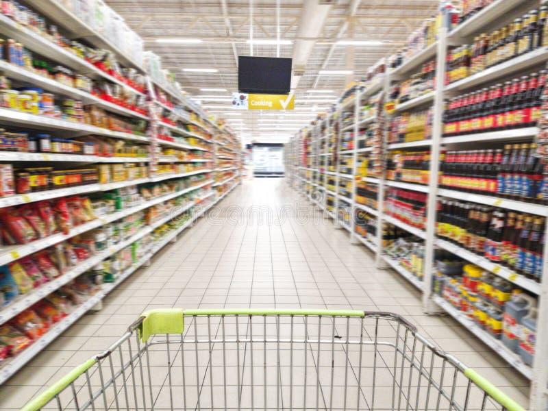 Wózek na zakupy z abstraktem zamazywał supermarket nawę z kolorowymi towarami na półkach przy tłem, znak produkt dla gotować fotografia stock