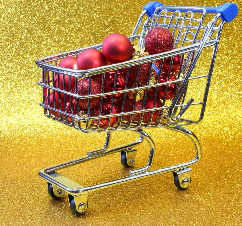 Wózek na zakupy z czerwonymi dekoracyjnymi Bożenarodzeniowymi piłkami i złotym bac zdjęcia royalty free