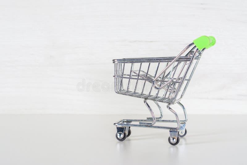 Wózek na zakupy z jasnozielonym treserem Targowy spacerowicz na jasnopopielatym tle obrazy stock