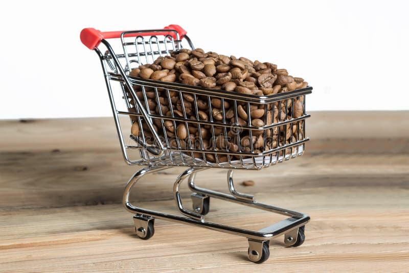 Wózek na zakupy z kawowymi fasolami na drewnianym stole zdjęcie stock