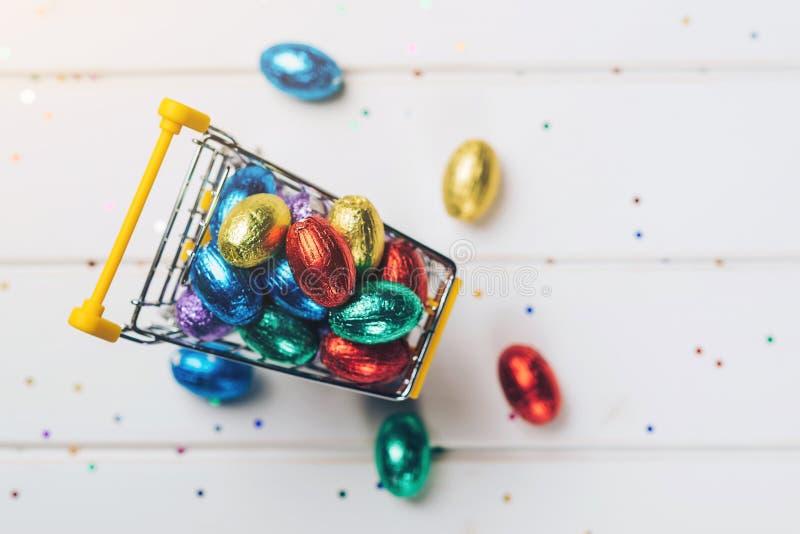 Wózek na zakupy z kolorowymi Easter jajkami na białym drewnianym tle zdjęcia stock