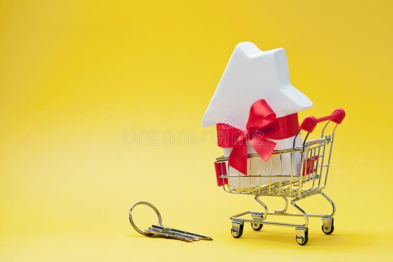 Wózek na zakupy z mały dom dekorującym bielu łęku faborkiem, czerwoną wiązką klucze na żółtym tle i Kupować nowego dom, prezent obraz stock