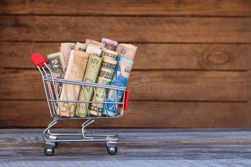 Wózek na zakupy z pieniądze od różnych krajów: dolary, euro, hryvnia, ruble obraz stock