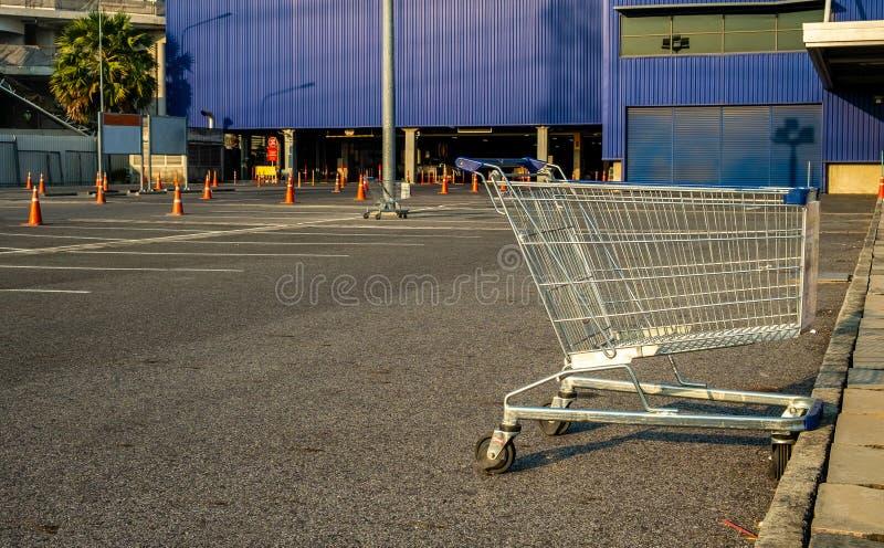 Wózek na zakupy z ruchu drogowego rożkiem w sklepu parking, błękitny tło obrazy stock