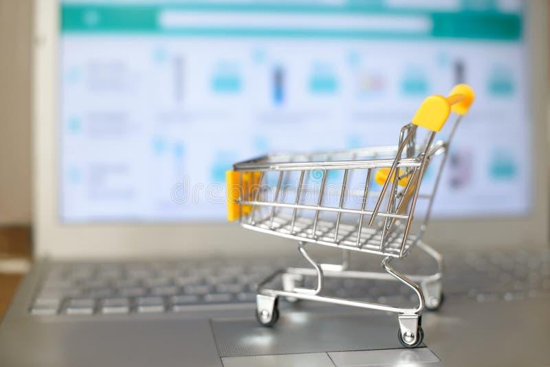 Wózek na zakupy zabawka na klawiaturze przed laptopu ekranem z internet stroną internetową na nim zdjęcia royalty free