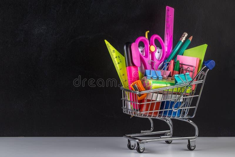 Wózek na zakupy zaopatrujący z szkolnymi dostawami i blackboard zdjęcia stock