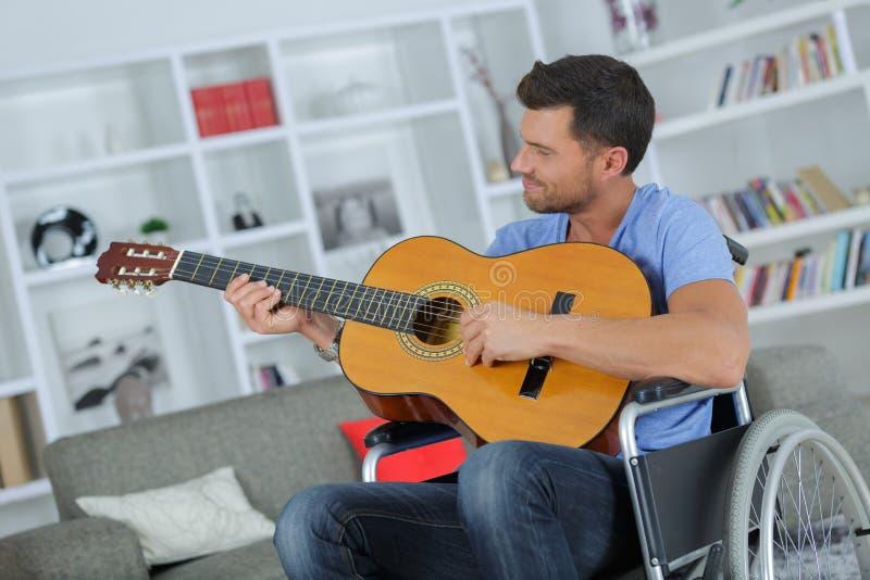 Wózka inwalidzkiego użytkownik bawić się gitarę zdjęcie stock