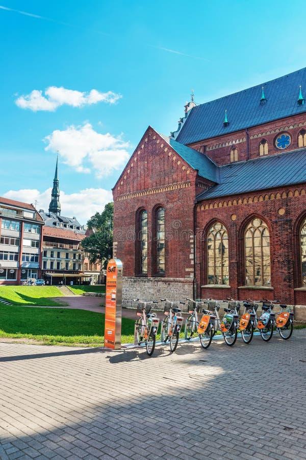 Wölben Sie sich Quadrat mit Fahrrädern und Helm St. Peter Church Riga lizenzfreie stockbilder