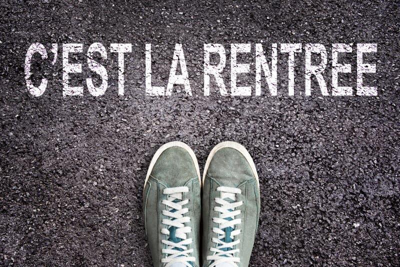 Wörter C ` est-La rentree Bedeutung zurück zu der Schule, die auf Asphaltstraße mit Turnschuhschuhen geschrieben wird, Highschool stockfotos