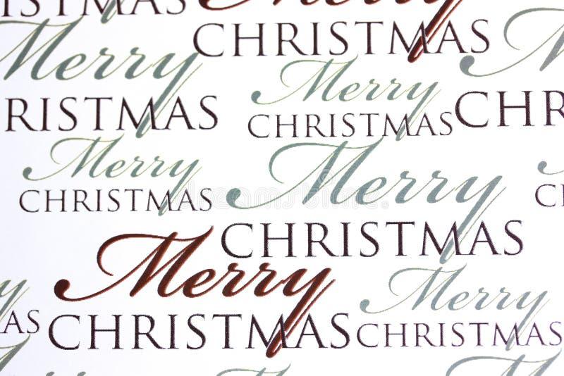 Wörter der frohen Weihnachten auf Papierhintergrund lizenzfreie stockbilder