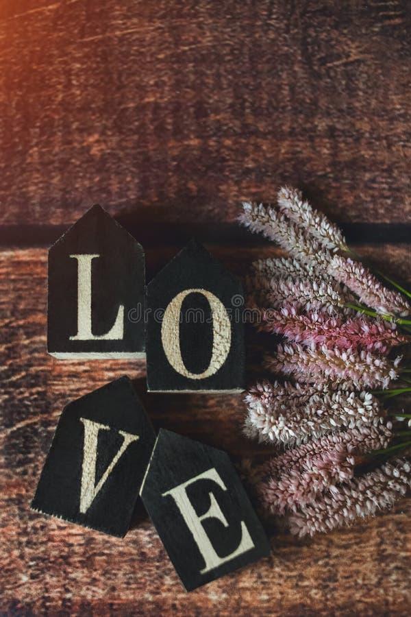 Wörter der Liebe von den Würfeln mit Sommerblumen, getont stockfotografie