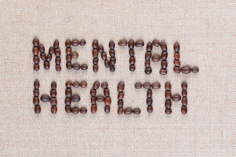 W?rter der psychischen Gesundheit von den Kaffeebohnen auf Leinensegeltuch, Schuss nah oben lizenzfreies stockfoto