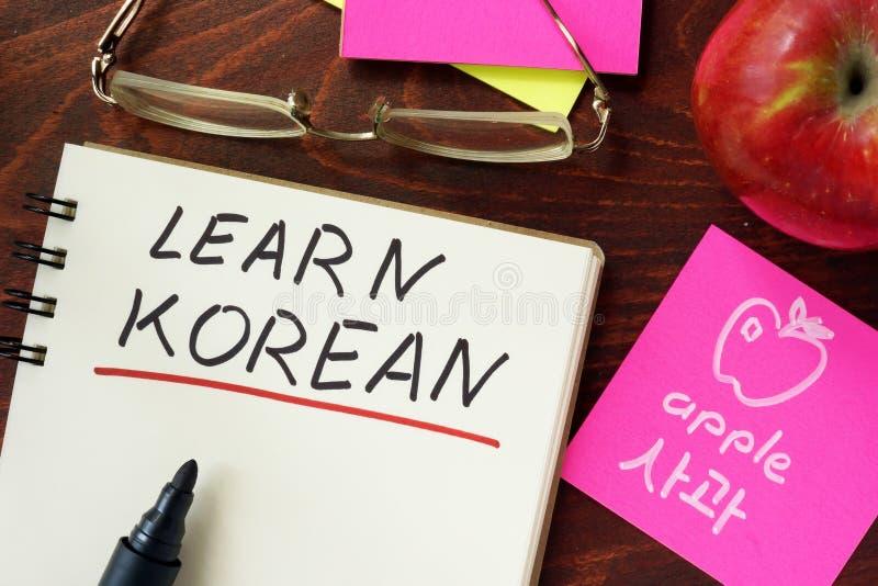 Wörter lernen Koreanisch, das in den Notizblock geschrieben wird lizenzfreie stockfotos