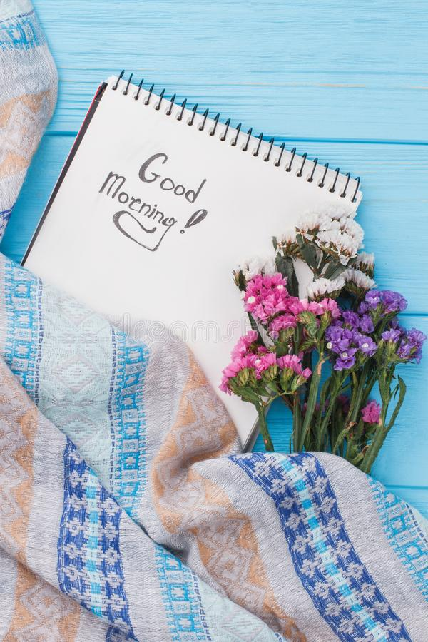 Wünschen Sie guten Morgen auf Notizbuch Seiten- und staticeblumen stockfotografie