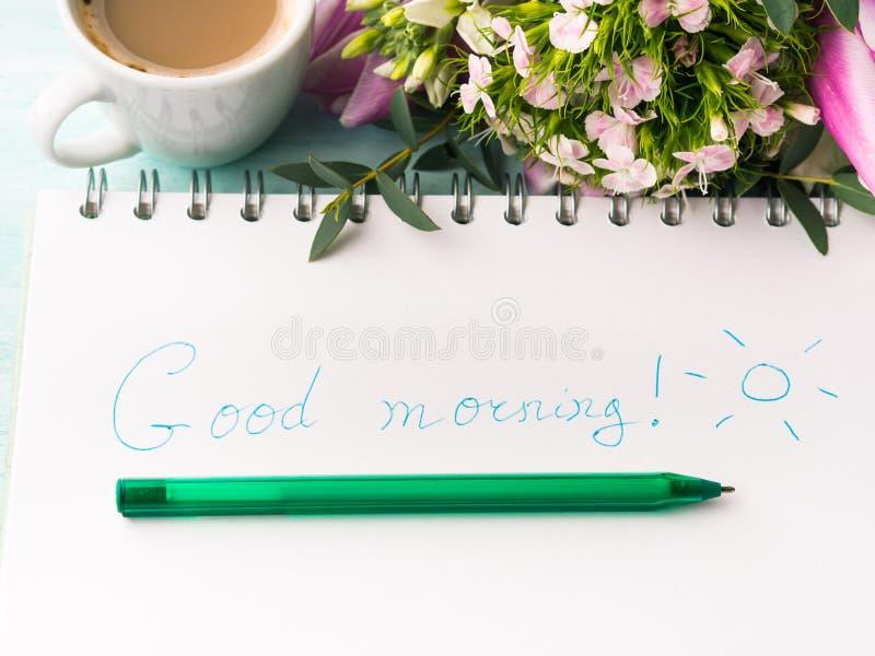 Wünschen Sie guten Morgen auf Notizbuchseite und -kaffee lizenzfreies stockbild