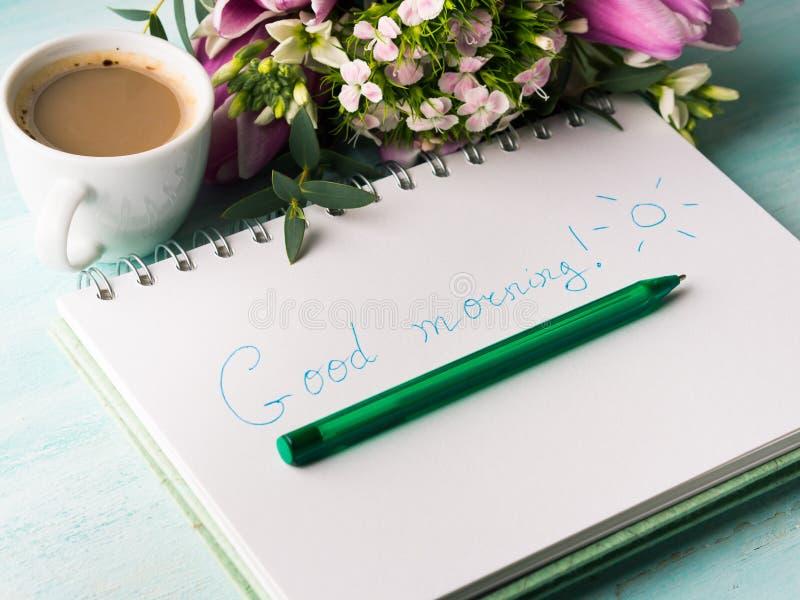 Wünschen Sie guten Morgen auf Notizbuchseite und -kaffee stockbilder