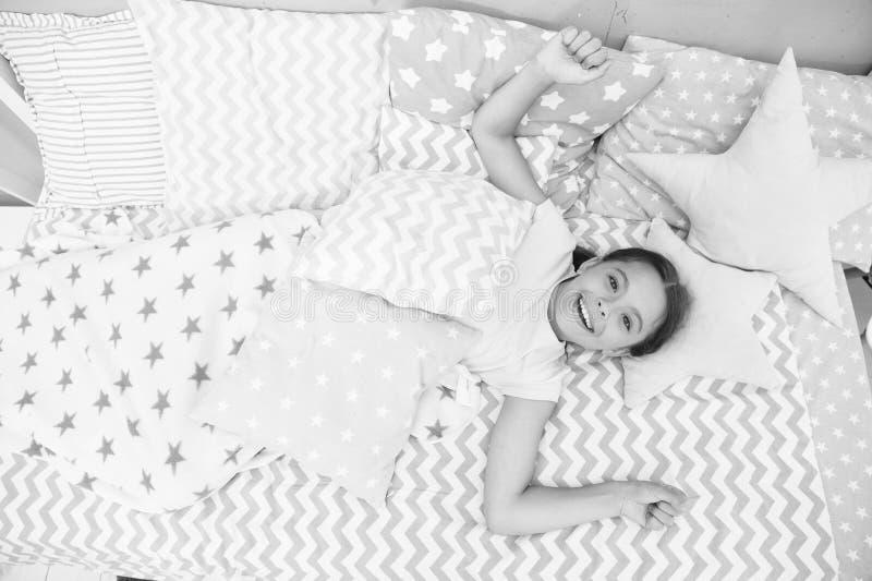 Wünschen Sie ihren guten Morgen Mädchenkind gelegt auf Bett ihr Schlafzimmer Kind wach und voll von der Energie Angenehme Zeit en lizenzfreies stockbild