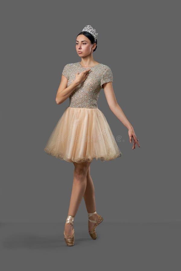 Würdevolle Ballerina, die das beige Kleid aufwirft im Studio trägt lizenzfreie stockfotografie