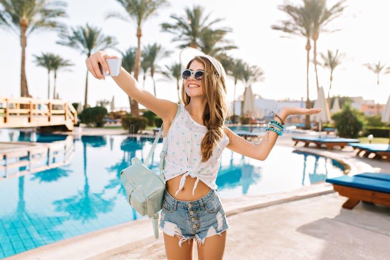 Würdevolle Tänzerin in den modischen Armbändern und weißen im Hut, die selfie bevor dem Schwimmen im Freibad macht Herrliche Jung stockbilder