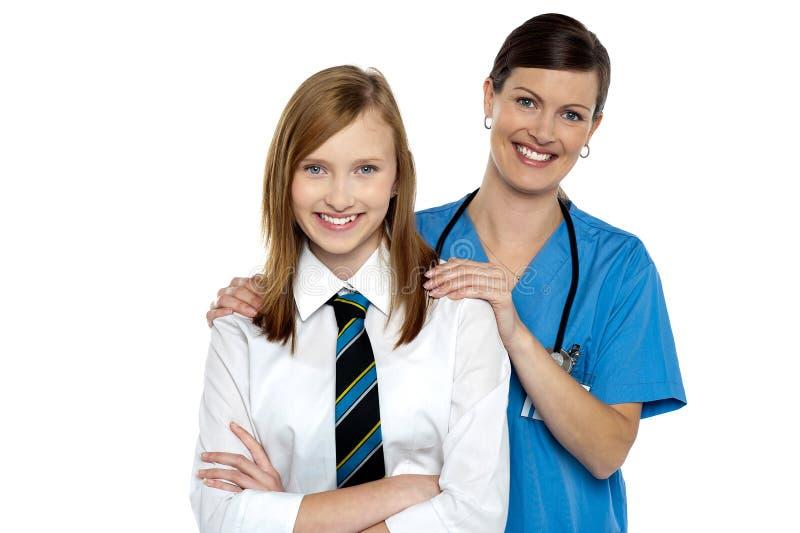 Würdevoller Doktor, der mit ihrem Jugendpatienten aufwirft lizenzfreies stockbild