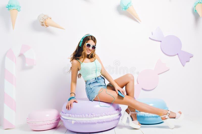 W?rdevolles lachendes M?dchen, welches die auf den Fersen gefolgten Sandalen sitzen auf purpurrotem Makronenstuhl und h?render Mu lizenzfreies stockfoto