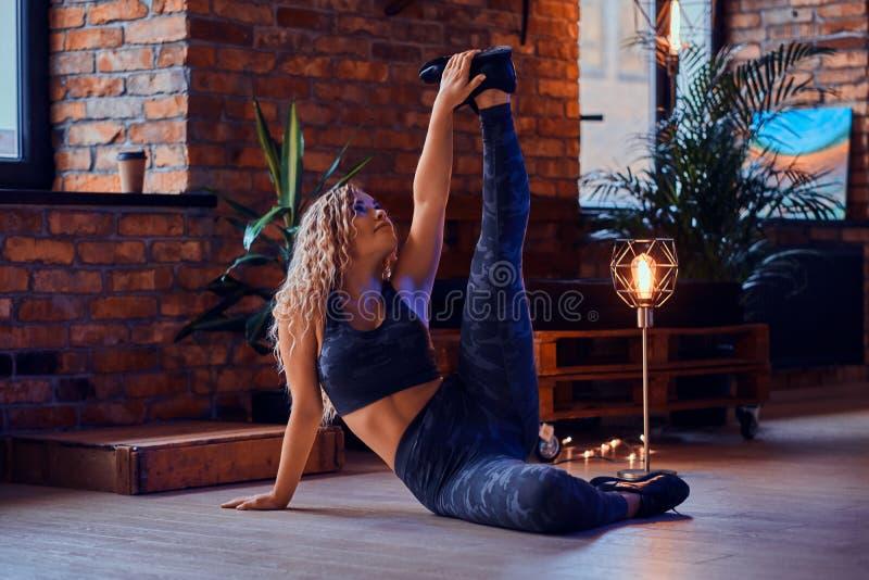 Würdevolles sexy Plusgrößenmodell tut Yoga am modernen Dachboden lizenzfreies stockbild