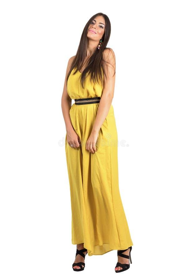 Würdevolles weibliches Mode-Modell im gelben Kleid, das an der Kamera aufwirft stockfotos