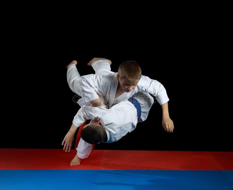 Würfe mit dem Fallen durchführend, bilden Athleten im karategi aus lizenzfreies stockfoto