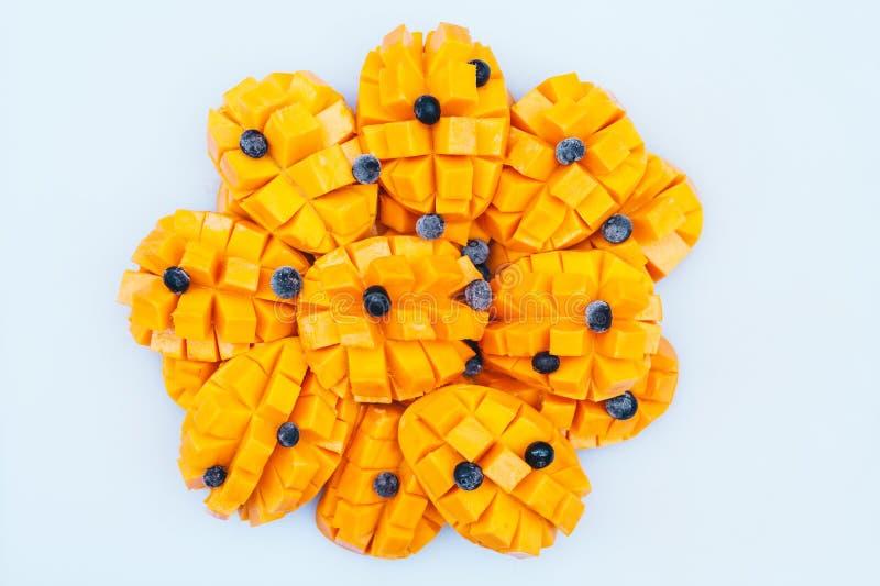 W?rfel der gelben reifen Mango mit der Blaubeere lokalisiert ?ber wei?em Hintergrund Frische Fr?chte Gesunde Nahrung Mango-Scheib lizenzfreies stockfoto