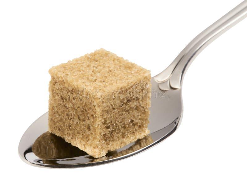 Würfel des braunen Zuckers auf Löffel stockbilder