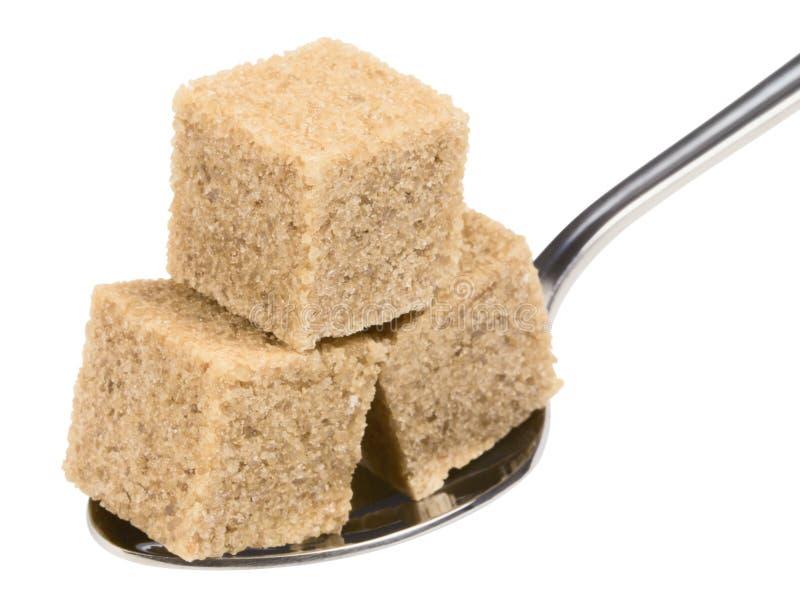 Würfel des braunen Zuckers auf Löffel lizenzfreie stockfotografie