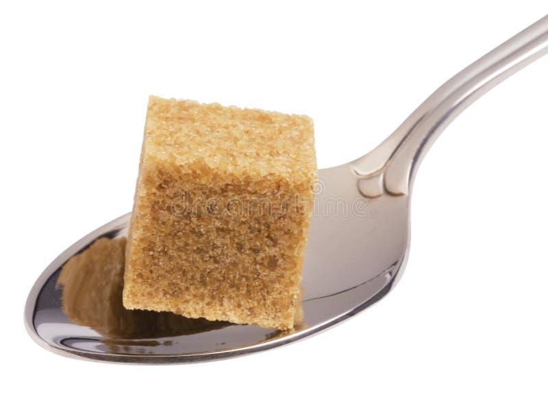 Würfel des braunen Zuckers auf Löffel stockbild