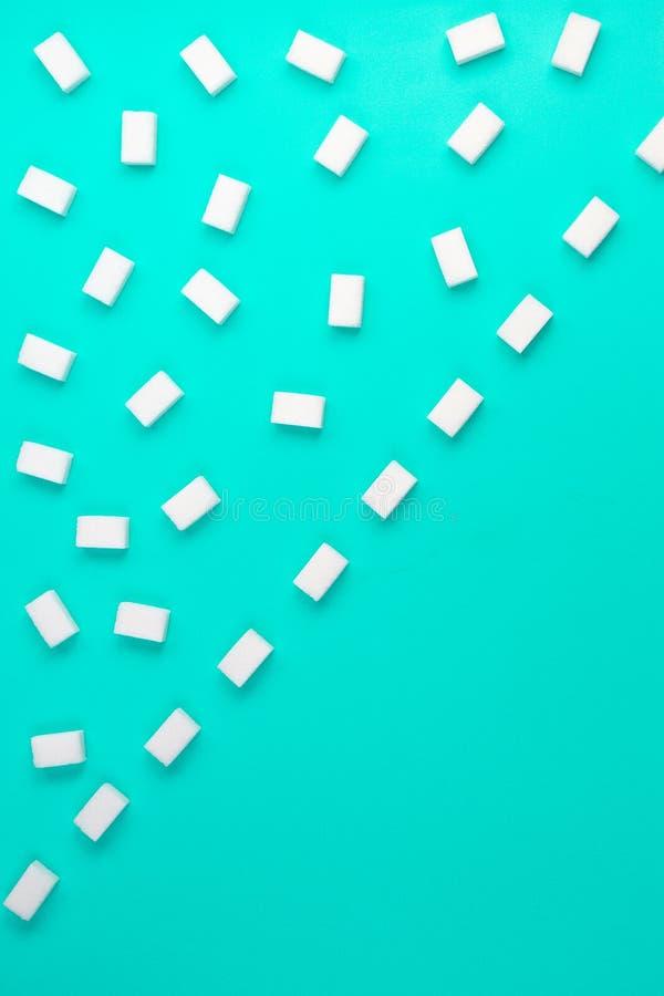 Würfel des raffinierten Zuckers vereinbarten in den diagonalen Linien auf blauem Hintergrund stockfoto